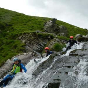 people sliding down waterfall - canyoning with How Stean Gorge's Team