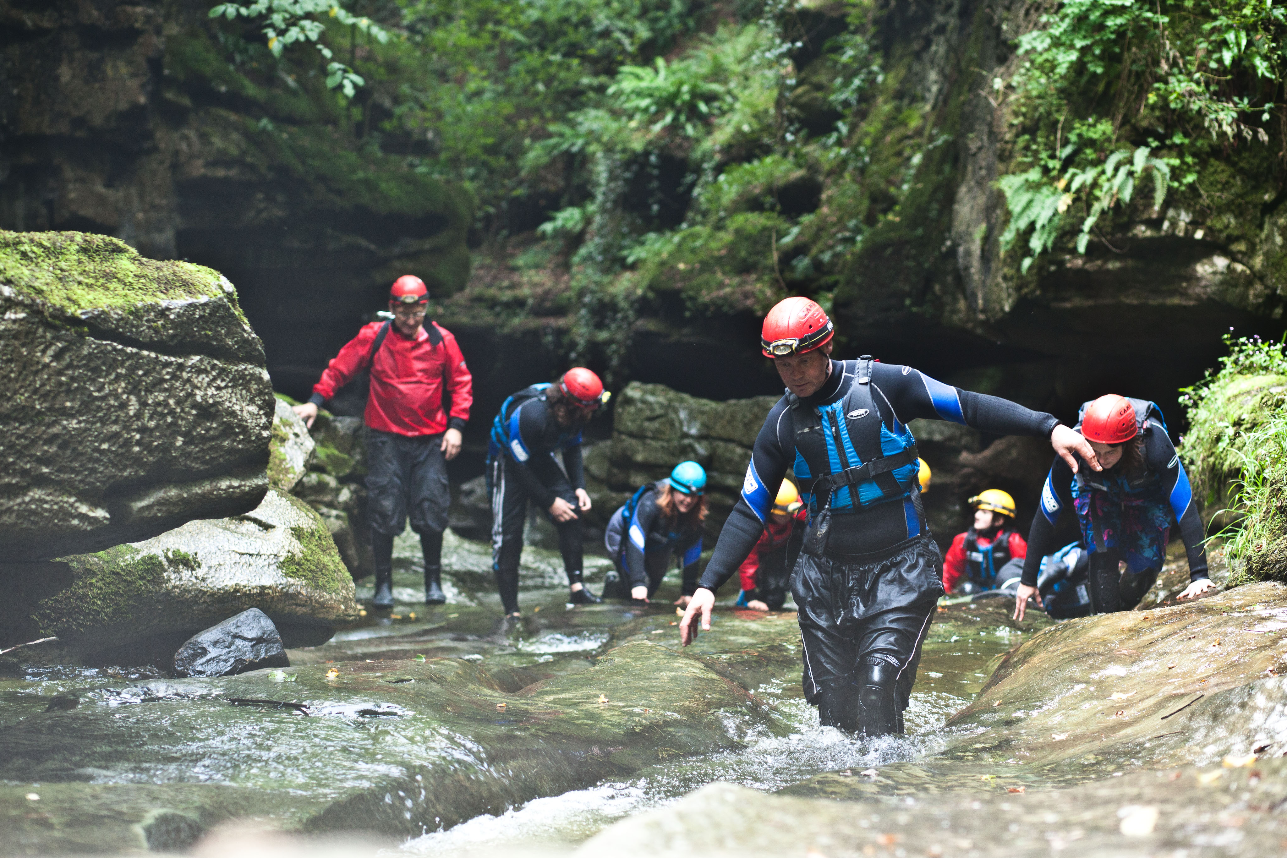 Group Gorge walking against the water current at How Stean Gorge, Yorkshire