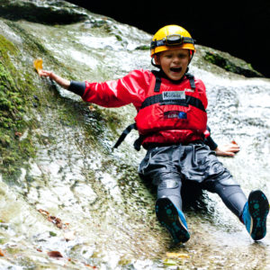 School child sliding down spout whilst gorge walking at How Stean Gorge, Yorkshire Dales. Outdoor activities