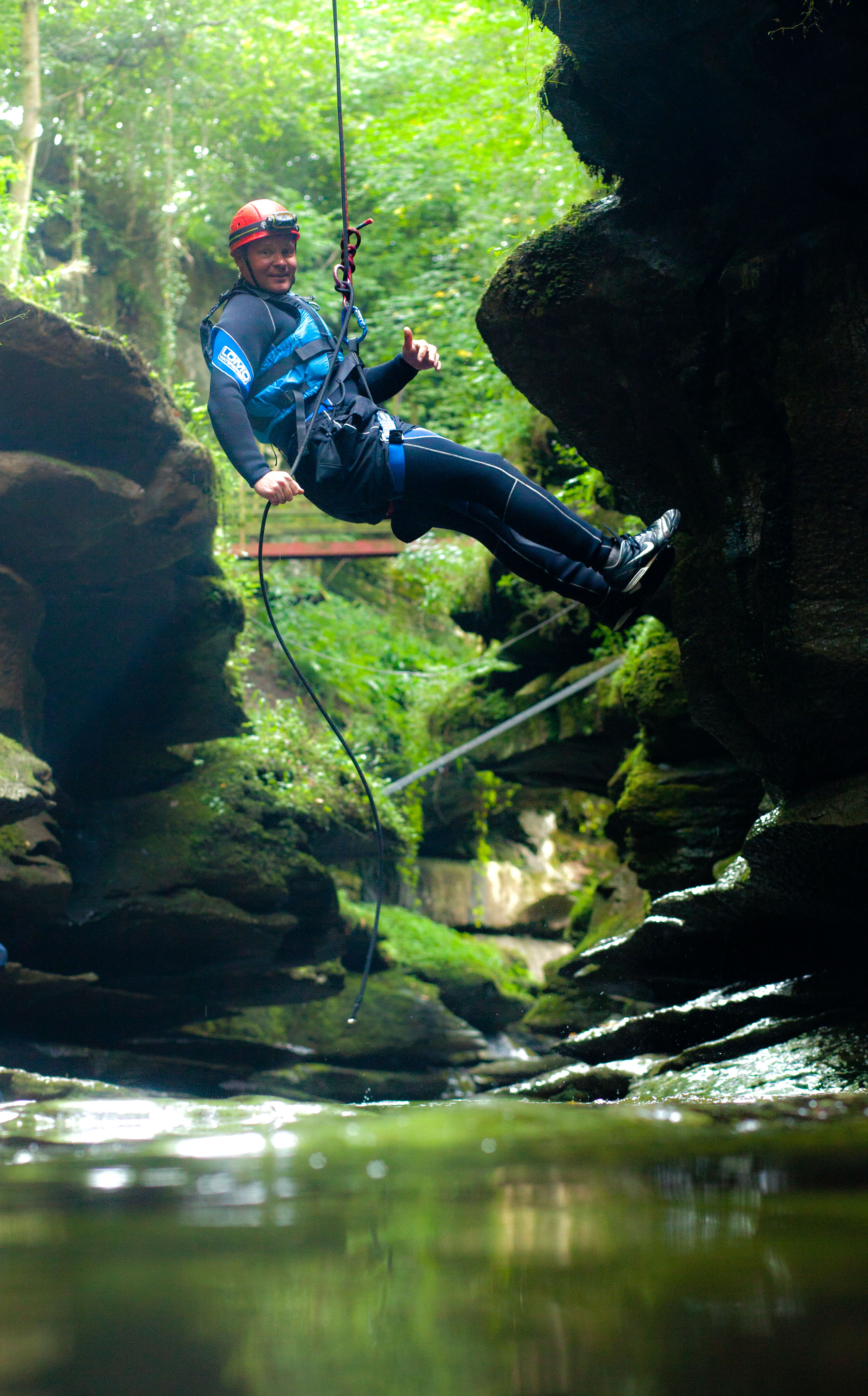 man abseiling into How Stean Gorge beck