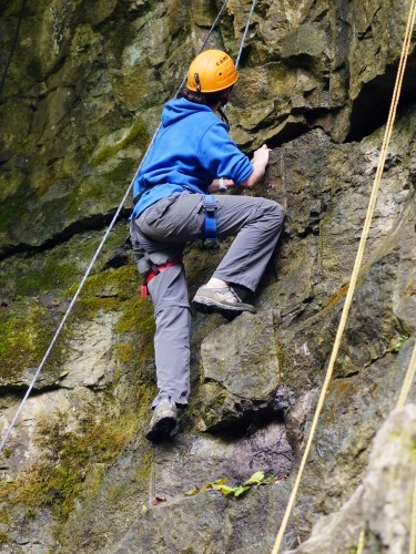 Person rock climbing up rock face at How Stean Gorge in Yorkshire Dales