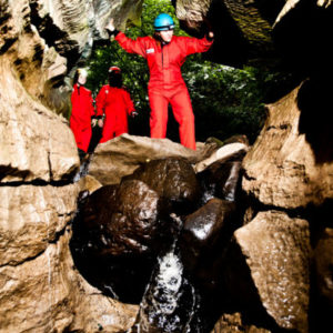 Girl looking to climb down waterfall whilst caving at How Stean Gorge in Yorkshire