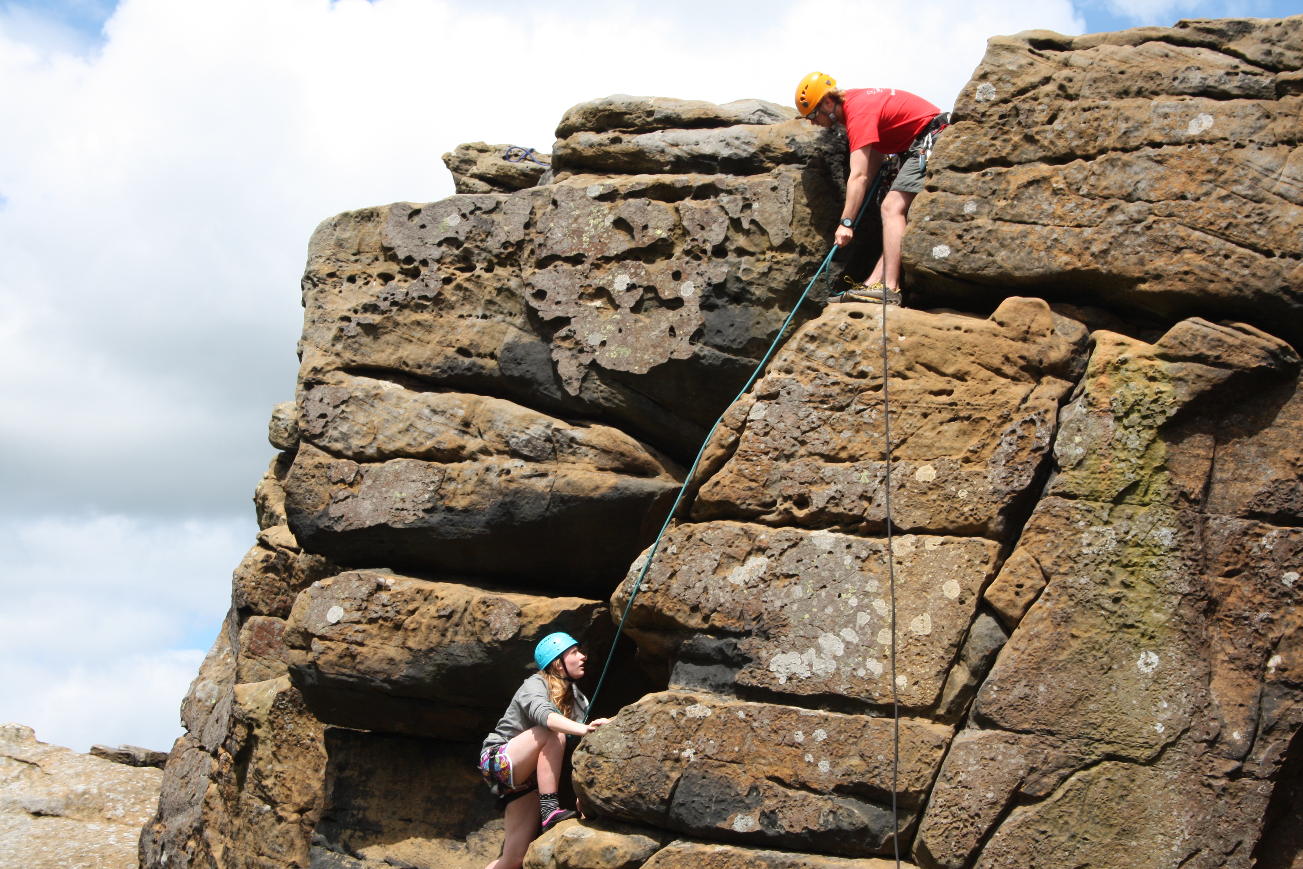instructor helping a beginner rock climber ascend the rock face